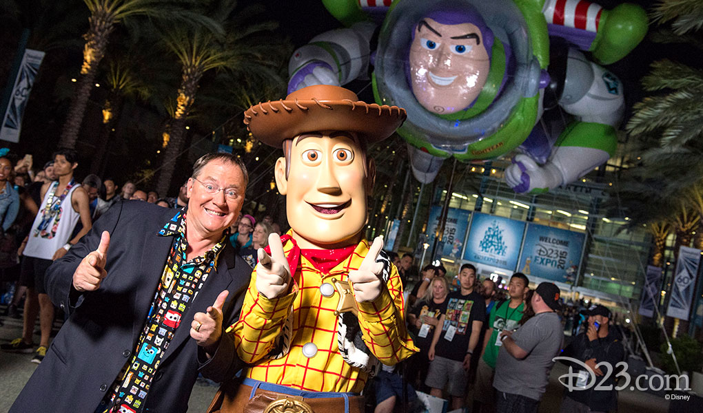 photo of John Lassater with life-sized character Woody and a huge inflatable Buzz Lightyear floating overhead