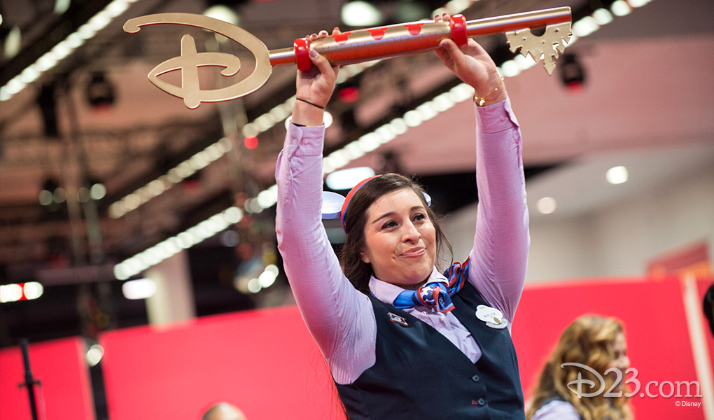 photo of Disney Store Key Held High by cast member in Mickey Mouse cap on opening day of D23 EXPO 2015