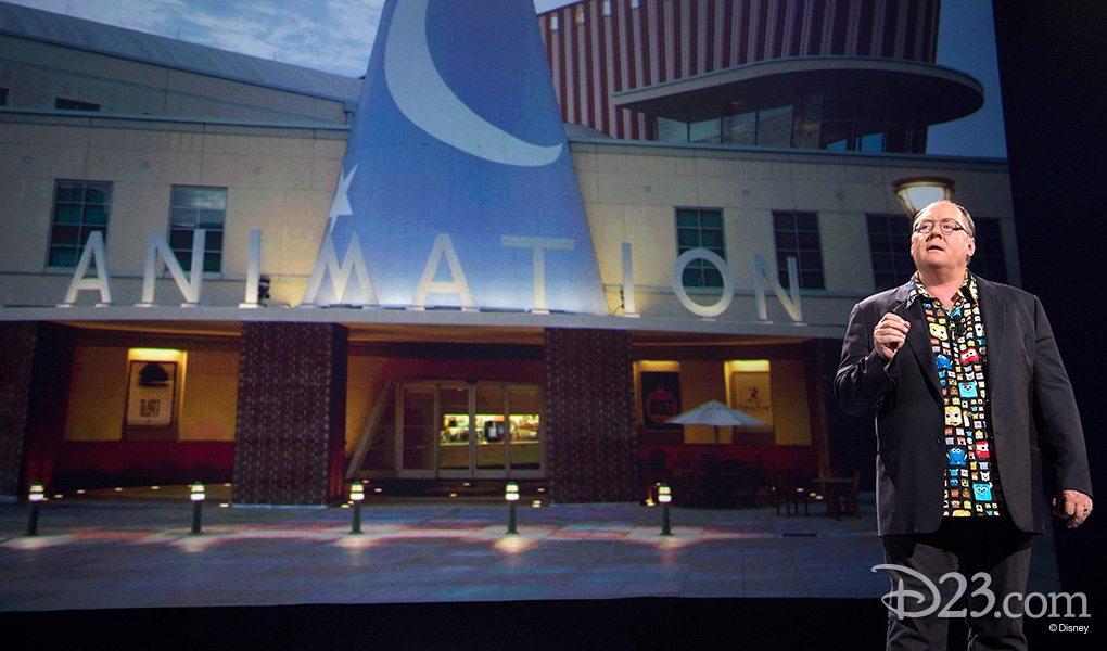 photo of John Lasseter on stage in front of projected image of the Walt Disney Animation building