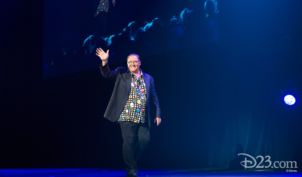 photo of John Lasseter waving as he walks on stage at the Walt Disney Animation - Pixar Animation event at D23 EXPO 2015