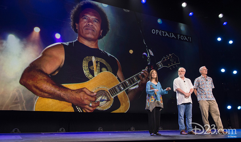 photo of Osnat Shurer, Ron Clements, John Musker on stage featuring background image of singer-songwriter Te Vaka Featuring Opetaia Foai from the group Te Vaka at D23 EXPO 2015
