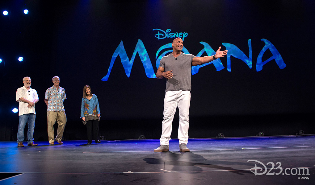 """photo of Osnat Shurer, Ron Clements John Musker with Dwayne """"The Rock"""" Johnson on stage at D23 Expo 2015"""