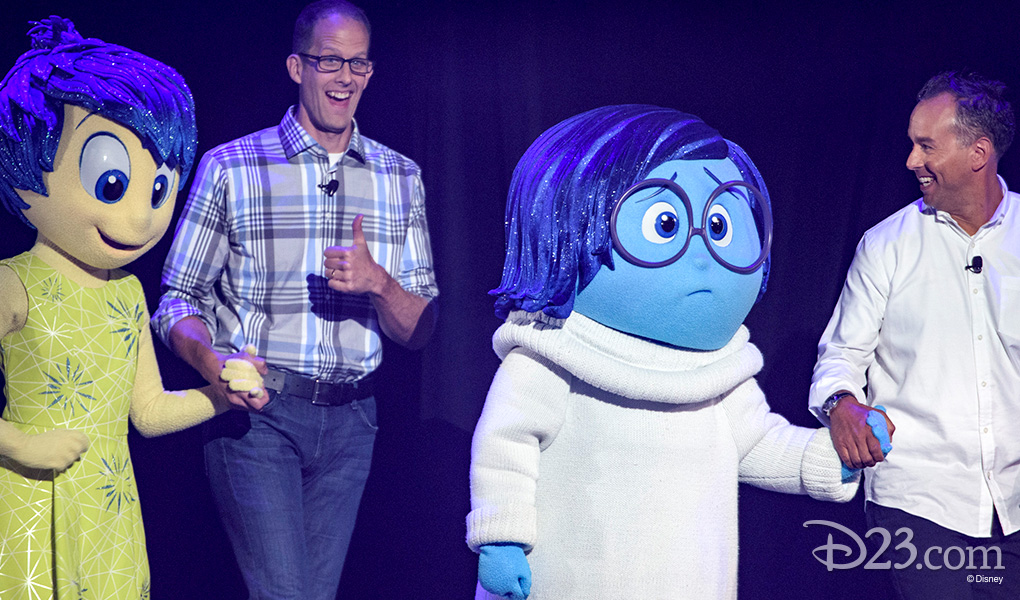 photo of Pete Docter, Jonas Rivera each leading a life-size character from Inside Out by the hand onto the stage