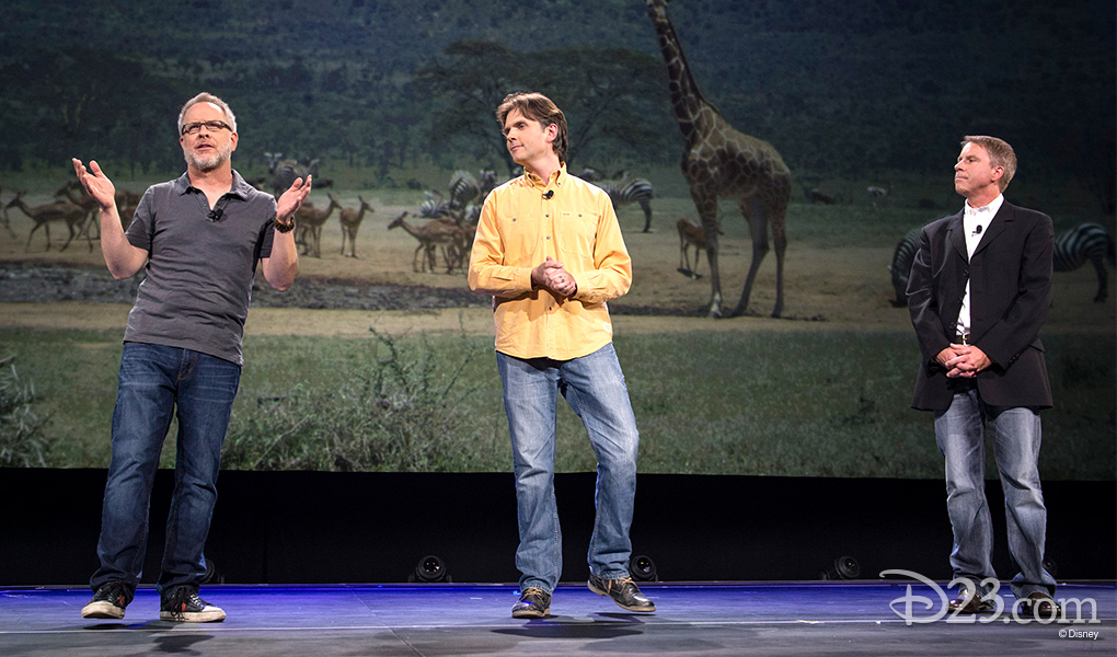photo of Rich Moore, Byron Howard, and Clark Spencer On Stage in front of projected image of wild zebra, giraffes and other animals spread across a wide African savanna