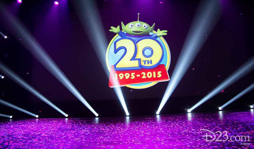photo of elaborately lit stage with footlight spotlights beaming upwards in a semi-circle around large graphic of Toy Story's Alien and the text 20th 1995 - 2015