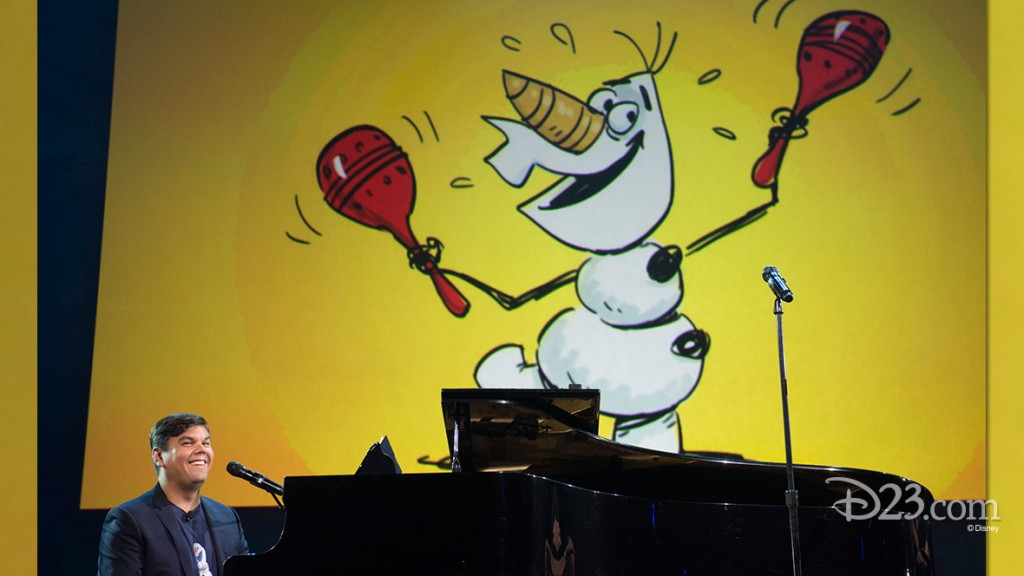 photo of Bobby Lopez seated at piano beneath large illustration of Olaf the snowman