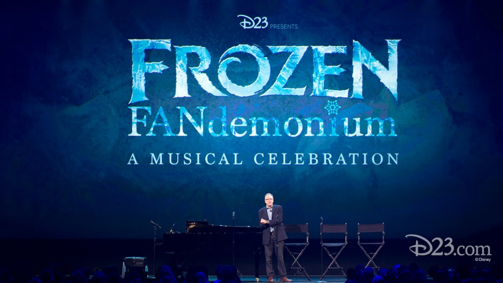 photo of Chris Monton, president of Walt Disney Music, standing on stage beneath a large graphic for Frozen FANdemonium A Musical Celebration