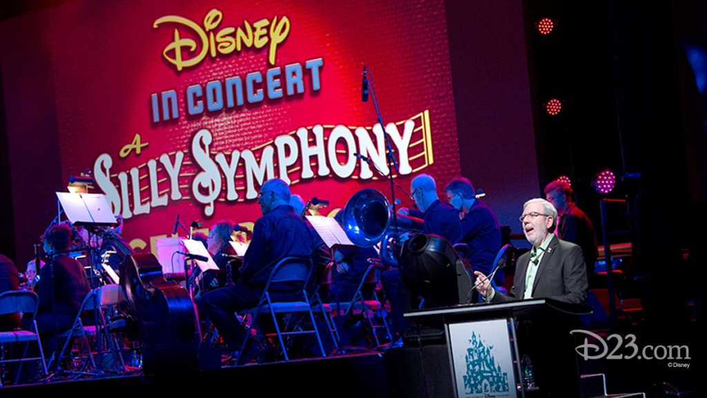 photo of Leonard Maltin at podium beside orchestra on stage beneath a banner Disney in concert Silly Symphony
