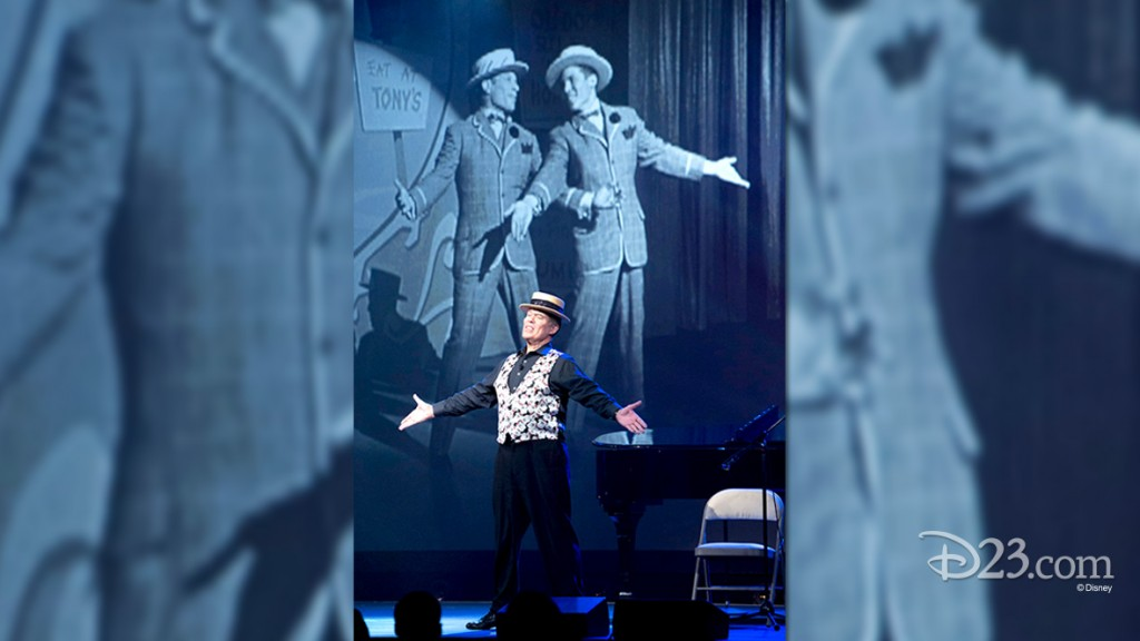 photo of male singer in flat topped boater hat with arms spread standing in front of projected image of himself half a century earlier in the same pose on stage with a co-singer
