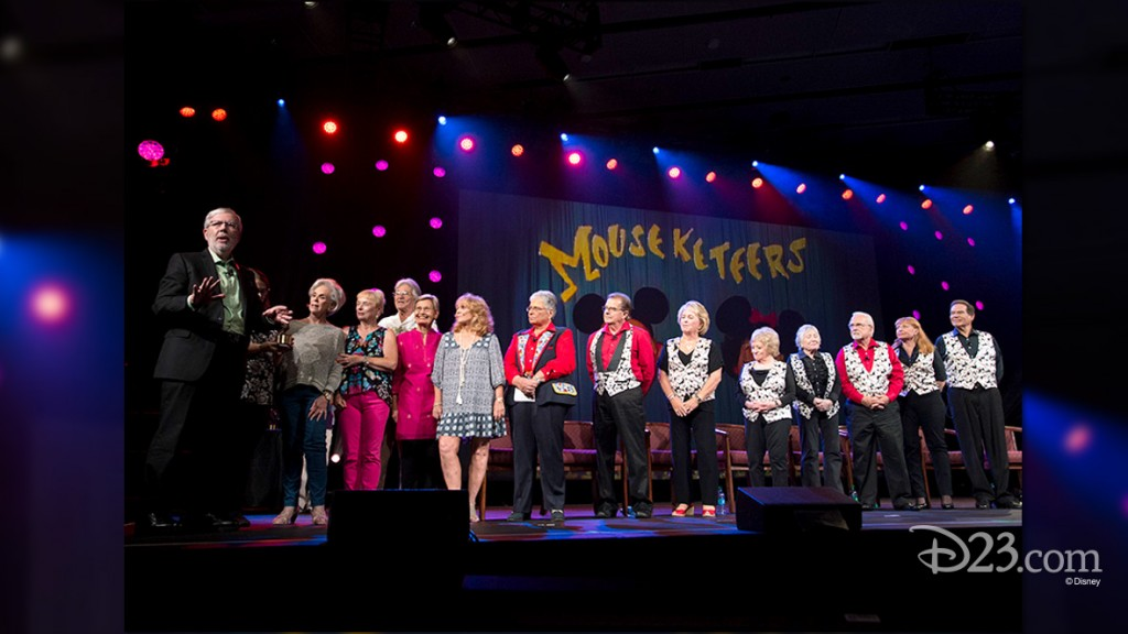 photo of Leonard Maltin and fourteen members of original Mouseketeers lined up on stage