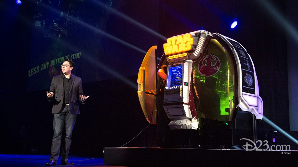 photo of presenter on stage with brightly lit Star Wars Battle Pod