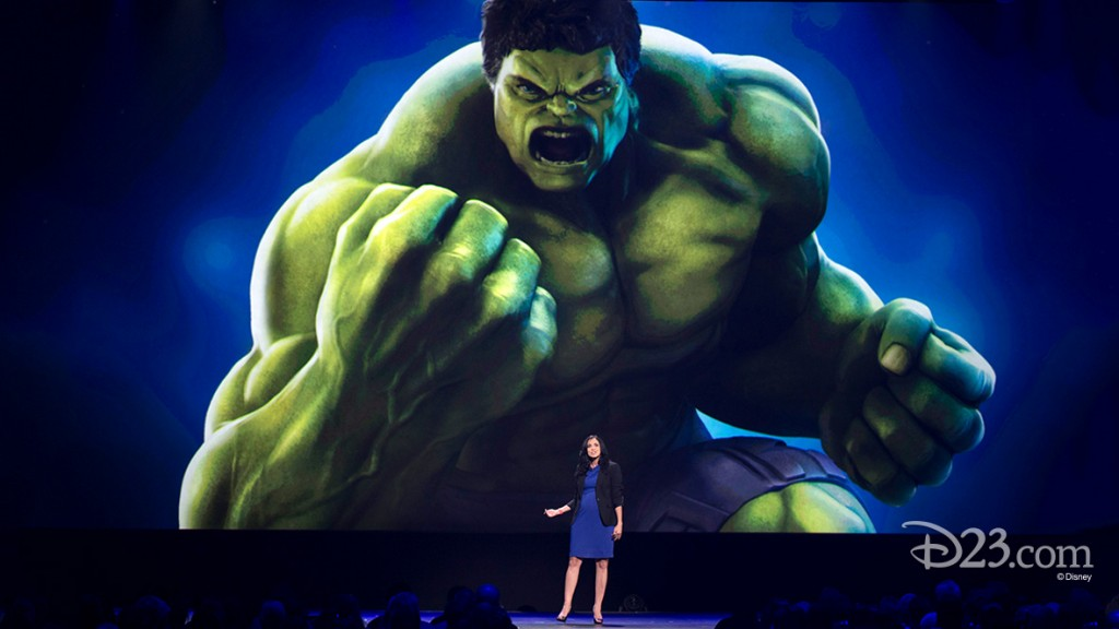 photo of Afsoun Yazdian, director of product management for Playmation, standing on stage beneath gigantic graphic of The Hulk angrily brandishing his fists