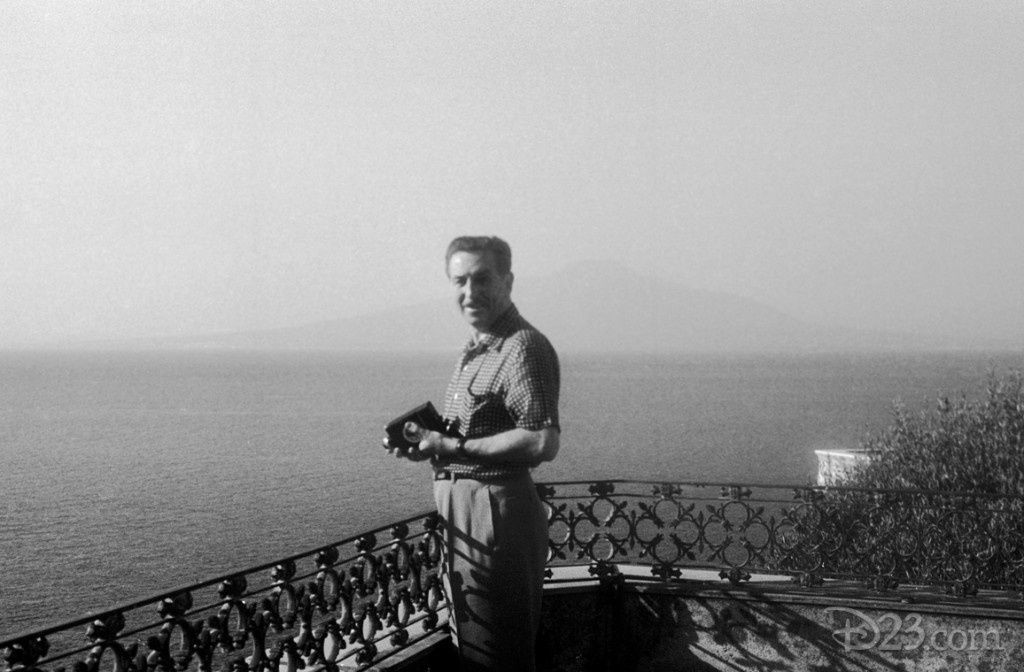 One of the world's most innovative filmmakers, Walt wouldn't travel all the way to Italy without a movie camera. Here he is seen with a 16 mm. movie camera in a candid moment along the Italian coast during the 1951 trip.