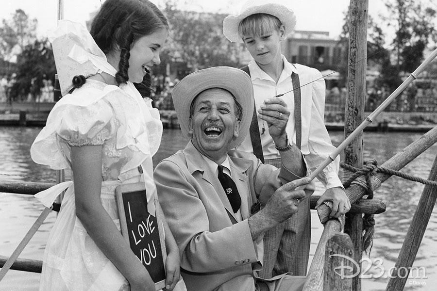 Walt Disney laughing with kids on Tom Sawyer Island.
