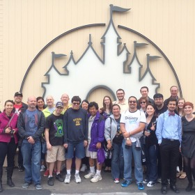 D23 Members standing by the Disney mural at the Walt Disney Studio Lot