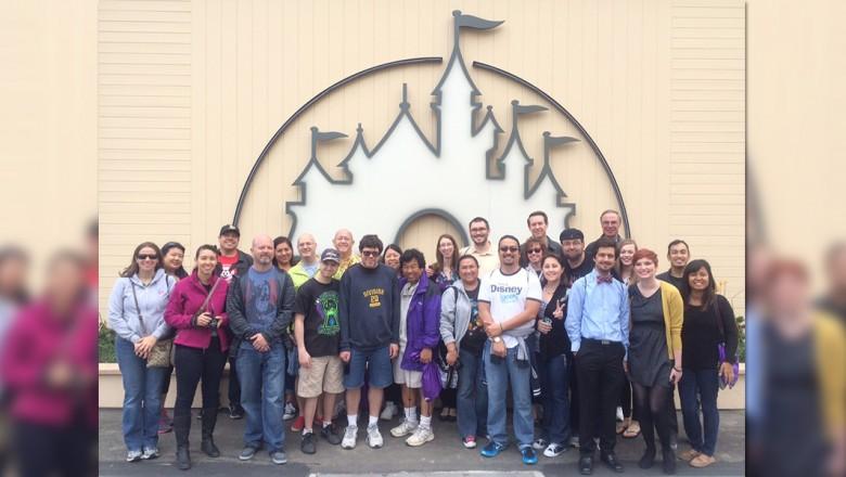D23 Members standing by the Disney mural at the Walt Disney Studio Lot