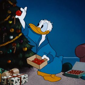 Donald Duck placing an ornament on the Christmas tree