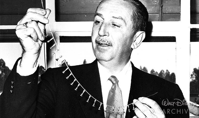 Walt Disney holding his Oscar charm necklace