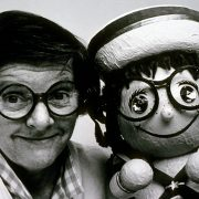 """Joyce Carlson with posing with a remarkably similar """"it's a small world"""" doll."""