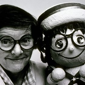 "Joyce Carlson with posing with a remarkably similar ""it's a small world"" doll."