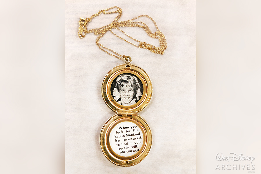 One of the gold lockets with a photo of Pollyanna and a quote inside.